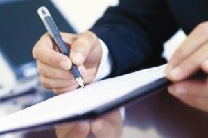 Businessman+signing+document+at+his+desk,+close-up+of+hands