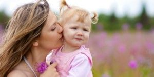 Mother kissing daughter in meadow outdoor